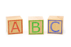 ABC letters on three brown wooden cubes lined up Stock Photos