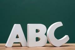 Abc märker framme av bräde Arkivbilder