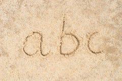 Abc märker skriftligt i sand Fotografering för Bildbyråer