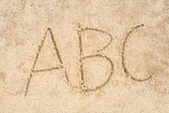 Abc märker skriftligt i sand Arkivfoton