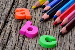 Abc-ord med färgrika blyertspennor på tabellen Fotografering för Bildbyråer