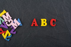 ABC redacta en el fondo negro del tablero compuesto de letras de madera del ABC del bloque colorido del alfabeto, copia el espaci Imagenes de archivo
