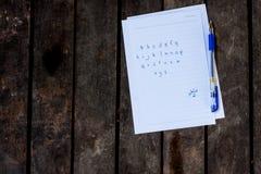 Abc skrev ett papper på trägolvet Arkivbild