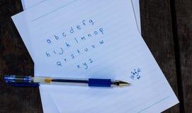 Abc skrev ett papper på trägolvet Arkivfoton