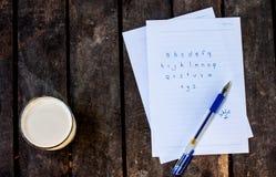 Abc skrev ett papper på trägolvet, och ett exponeringsglas av sojabönor mjölkar Arkivfoton