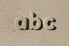 Abc som är skriftlig i sandbokstäver Royaltyfri Foto