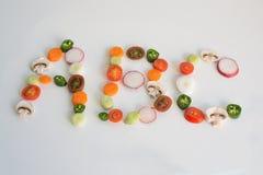 abc som stavas ut från grönsakskivor Royaltyfria Bilder