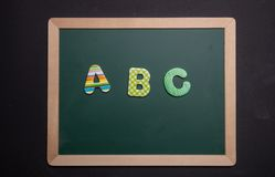 Abc text on green board with wooden frame, black background royalty free stock photo