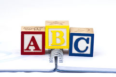 ABC in wooden blocks. Over spiral of notebook Stock Image