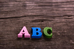 ABC word made of wooden letters. ABC word made from colored wooden letters on an old table. Concept Stock Photos