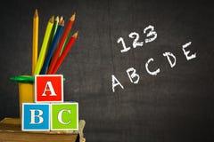 ABC y lápices multicolores en el libro viejo Imagen de archivo