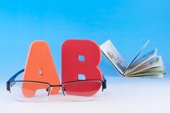 abcbokstäver, glasögon och bok Arkivfoton