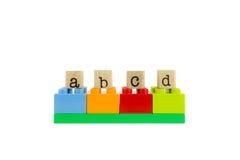 Abcd ord på trästämplar och färgrika leksakkvarter Royaltyfri Fotografi