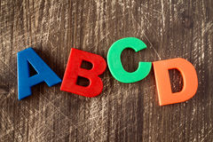 ABCD spelling from plastic letters. On wooden background Stock Photography