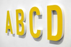 ABCD yellow alphabet letters. Mounted on a white wall with shadow viewed at an oblique angle with D in the foreground Royalty Free Stock Photos
