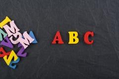 abcord på svart brädebakgrund som komponeras från träbokstäver för färgrikt abc-alfabetkvarter, kopieringsutrymme för annonstext Arkivbilder