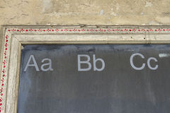 ABCs. Old school blackboard in wooden frame with abc's across the top Stock Photography
