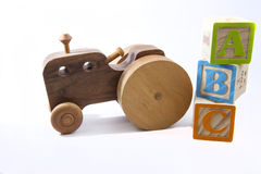 ABCs and old toy car or tractor. Wooden toy ABC blocks and old fashioned handmade wooden car or tractor Stock Photo