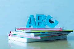 ABCs symbols placed on a stack of educational children`s books. Closeup of books with plastic A,B, and C letters in blue tinted style Stock Photography