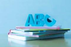 ABCssymbolen op een stapel onderwijskinderen` s boeken dat worden geplaatst Stock Fotografie