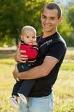 Abd joven del padre su pequeño hijo en parque Imagen de archivo