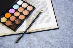 Abdeckstift, Make-upbürste, offenes Buch lizenzfreie stockfotografie