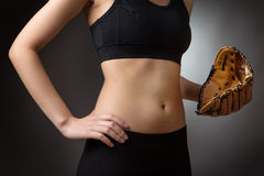 Abdomen with baseball glove. Close up shot of a slim young models abdomen, whilst wearing a baseball glove close to her abdomen on her left hand and her right Royalty Free Stock Photos