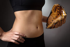 Abdomen with baseball glove. Close up shot of a slim young models abdomen, whilst wearing a baseball glove close to her abdomen on her left hand and her right Stock Images