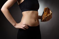 Abdomen with baseball glove. Close up shot of a slim young models abdomen, whilst wearing a baseball glove close to her abdomen on her left hand and her right Royalty Free Stock Photography