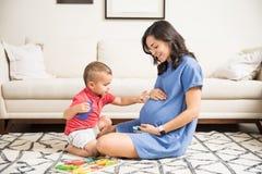 Abdomen conmovedor del muchacho inocente de la madre embarazada en casa Fotos de archivo libres de regalías