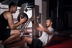 Abdomen del entrenamiento del hombre joven con el instructor Foto de archivo