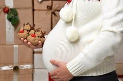 Abdomen embarazada de la mujer del topetón con la decoración de la Navidad del Año Nuevo Foto de archivo libre de regalías