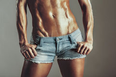 Abdomen muscled girls in shorts Royalty Free Stock Images
