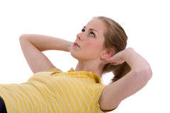 Abdominal curls. Pretty young woman doing abdominal curls on white background Stock Photos