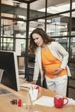 Stressed pregnant CEO suffering from muscle cramp stock photo
