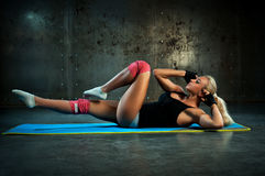 Abdominal exercises. Young woman doing abdominal exercises Stock Photography