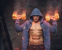 Abdominal male in a blue hoodie holds the burning dumbbells. Abdominal male in a blue hoodie holds the burning dumbbells with smoke on grey background royalty free stock image