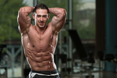 Abdominal Muscle Close-Up. Serious Men Standing In The Gym And Flexing Muscles stock image