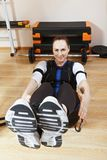Abdominal muscles training with EMS. Smiling caucasian woman makes abdominal muscles exercises in gym. She wears a suit with electrodes. Electric muscle Royalty Free Stock Photo