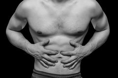 Abdominal pain. Unrecognizable man compresses the abdomen due to pain, monochrome image Stock Photos