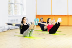 Abdominals training. Group make abdominals training exercises sitting on mats in a gym Stock Photos