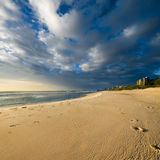 Abdrücke auf dem Strand mit interessanten Wolken Stockbild