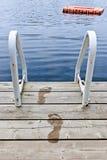 Abdrücke auf Dock am Sommersee Stockbild