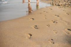 Abdrücke im Sand Menschliche Abdrücke, die weg von dem Zuschauer führen Eine Reihe von Abdrücken im Sand auf einem Strand im summ Stockfotos