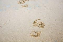 Abdrücke von Schuhen im Sand von der Front Stockfoto