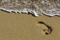 Abdruck am Strand mit Wellen Stockfotos
