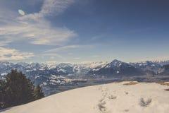 Abdruck und Tierbahnen auf Schnee mit Hintergrund des Gebirgszugs und des blauen Himmels Stockfotografie