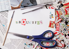 Abduction inscription made with cut out letters. On white paper Royalty Free Stock Images
