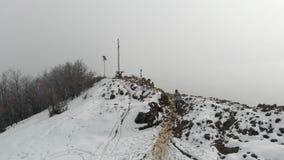 Abejón aéreo: el saludo de la mujer en el top de la montaña, el concepto de la pasión por los viajes de la aventura, la nieve y e almacen de video
