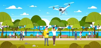 Abejón del vuelo de los pares en hombre y la mujer del parque que usa al control remoto Play With Copter al aire libre Fotografía de archivo